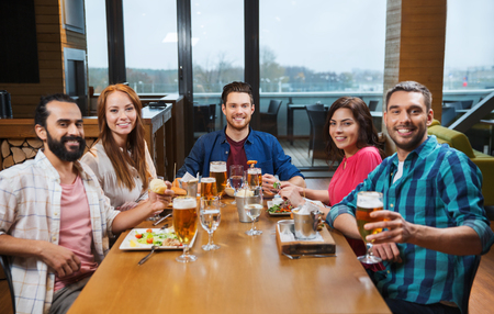 party friends: leisure, eating, food and drinks, people and holidays concept - smiling friends having dinner and drinking beer at restaurant or pub