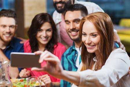 leisure, technology, friendship, people and holidays concept - happy friends having dinner and taking selfie by smartphone at restaurant Stock Photo