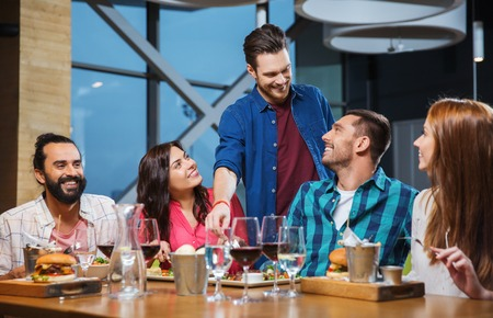 il tempo libero, mangiare, cibo e bevande, le persone e le vacanze concetto - sorridente amici a cena e bere vino rosso al ristorante