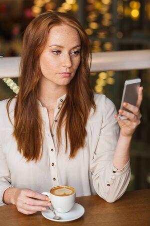 mujer sola: ocio, tecnología, estilo de vida y las personas concepto - mujer con el teléfono inteligente y el café en el restaurante