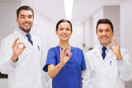 emergencia medica: clínica, profesión, la gente, la atención de la salud y la medicina concepto - grupo de médicos felices o médicos en el pasillo del hospital que muestran la muestra aceptable de la mano