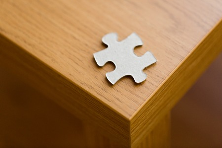 compatibility: business and connection concept - close up of puzzle piece on wooden surface Stock Photo