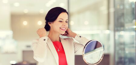 sale, consumerism, shopping and people concept - happy woman choosing and trying on pendant at jewelry store Stock Photo