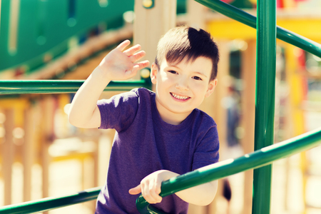 summer, childhood, leisure, gesture and people concept - happy little boy waving hand on children playground climbing frame Stock Photo
