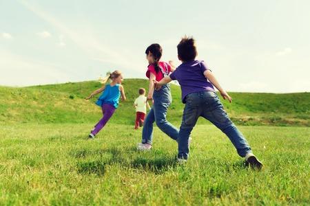 Estate, l'infanzia, il tempo libero e la gente il concetto - gruppo di bambini felici che giocano tag gioco e in esecuzione sul campo verde all'aperto Archivio Fotografico - 61743249