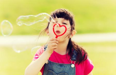 стиль жизни: лето, детство, досуг и люди концепции - маленькая девочка, дует мыльные пузыри через форму сердца кольцо на открытом воздухе Фото со стока