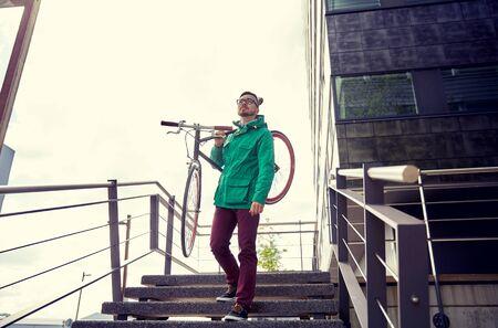 down stairs: la gente, el deporte, el estilo, el ocio y estilo de vida - hombre joven que lleva inconformista bicicleta fija del engranaje en el hombro por las escaleras en la ciudad