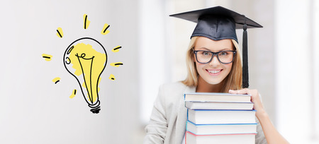 education, school, graduation and people concept - happy student girl or woman in graduation cap with stack of books over light bulb doodle Stock Photo