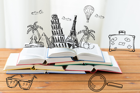 education, travel, literature, reading and knowledge concept - close up of books on wooden table with landmarks doodles