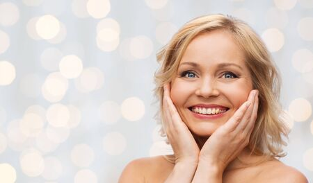 bare shoulders: beauty, people and skincare concept - smiling woman with bare shoulders touching face over holidays lights background