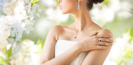 glamour luxury: glamour, beauty, jewelry and luxury concept - close up of beautiful woman with finger ring over natural spring cherry blossom Stock Photo