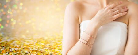 bride bangle: glamour, beauty, jewelry and luxury concept - close up of beautiful woman with golden ring and bracelet over golden holidays lights background