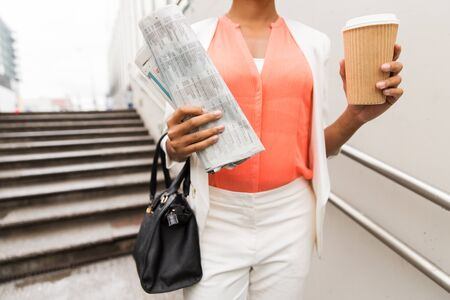 elegant staircase: business, drinks, lifestyle and people concept - close up of young african american businesswoman with coffee cup and newspaper walking downstairs to city subway