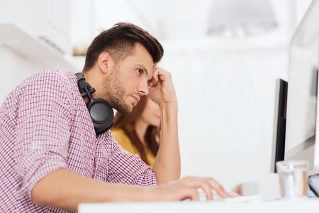 cansancio: plazo, puesta en marcha, la educación, la tecnología y el concepto de la gente - triste desarrollador de software estresado o estudiante con los auriculares y la computadora en la oficina Foto de archivo