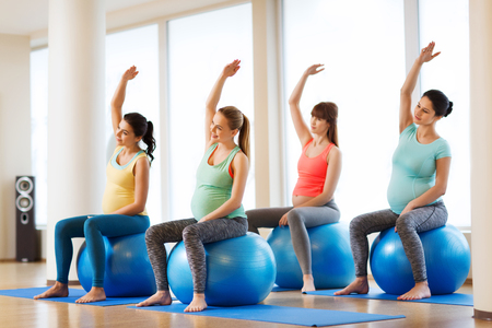 pregnancy, sport, fitness, people and healthy lifestyle concept - group of happy pregnant women exercising on ball in gym Reklamní fotografie - 61743367