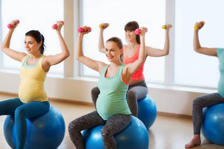 임신, 스포츠, 피트 니스, 사람들 및 건강 한 라이프 스타일 개념 - 체육관에서 공을 운동 dumbbells와 함께 행복 한 임신 여자의 그룹 스톡 콘텐츠
