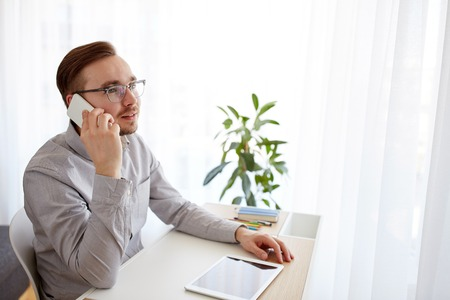 creative communication: business, startup, technology, communication and people concept - happy businessman or creative male worker with computer calling on smarphone at home office