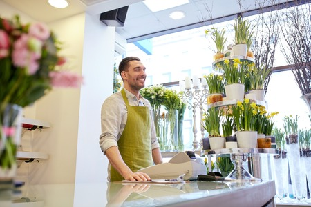 floristry: people, sale, retail, business and floristry concept - happy smiling florist man with cashbox standing at flower shop counter