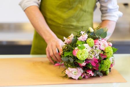 les gens, le shopping, la vente, la floristique et le consumérisme concept - close up de l'homme fleuriste emballage fleurs en papier à la boutique de fleurs