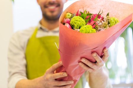 floristry: people, shopping, sale, floristry and consumerism concept - close up of happy florist man holding bunch wrapped in paper at flower shop