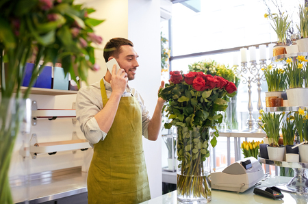 floristry: people, sale, retail, business and floristry concept - florist man with red roses calling on smartphone at flower shop counter Stock Photo
