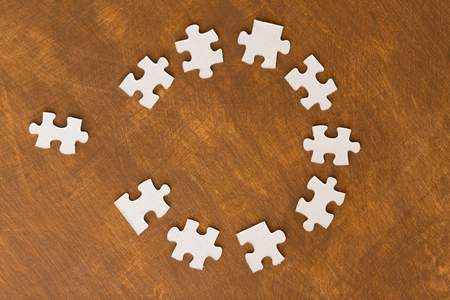 paper cut out: business and connection concept - close up of puzzle pieces on wooden surface