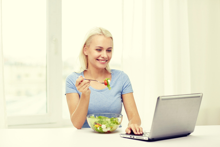 food concept: healthy eating, dieting, food, technology and people concept - smiling young woman with laptop computer eating vegetable salad at home