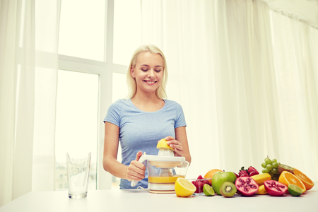 juice squeezer: healthy eating, vegetarian food, dieting and people concept - smiling woman with squeezer squeezing fruit juice at home
