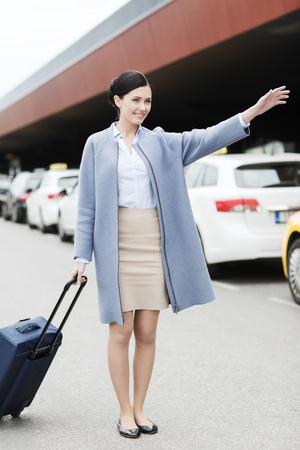 catching taxi: travel, business trip, people, gesture and tourism concept - smiling young woman with travel bag catching taxi at airport terminal or railway station