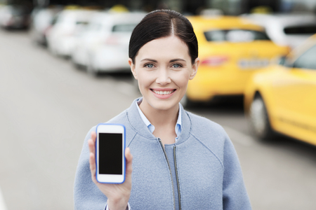 trip over: travel, business trip, people and tourism concept - smiling young woman showing smartphone blank screen over taxi station or city street Stock Photo