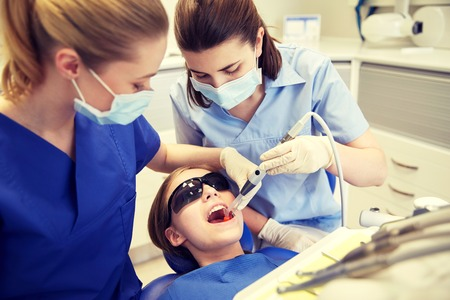 treating: people, medicine, stomatology and health care concept - female dentists with mirror and suction treating patient girl teeth at dental clinic office
