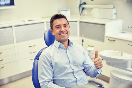 people, medicine, stomatology and health care concept - happy male patient sitting on dental chair and showing thumbs up at clinic office