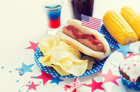 national holidays, celebration, food and patriotism concept - close up of hot dog with american flag decoration, potato chips and drinks on 4th july at party on independence day