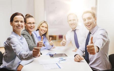 negocio, el éxito, la tecnología y el concepto de oficina - sonriendo equipo de negocios con ordenador Tablet PC y documentos que muestran los pulgares para arriba en la oficina