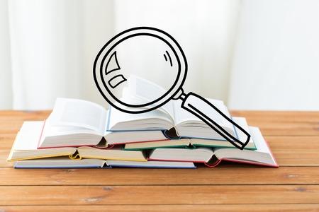 lupa: la educación, la escuela, la literatura, la lectura y el conocimiento concepto - cerca de libros sobre la mesa de madera con vidrio de aumento del Doodle