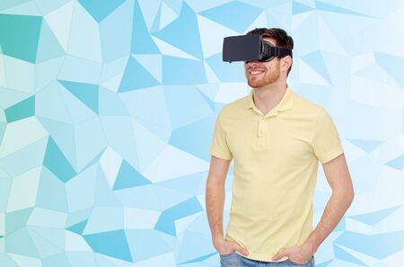 entertainment background: 3d technology, virtual reality, entertainment and people concept - happy young man with virtual reality headset or 3d glasses over blue low poly texture background, Stock Photo