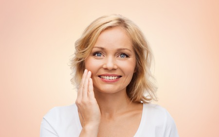 smiling face: beauty, people and skincare concept - smiling woman in white shirt touching face over beige background
