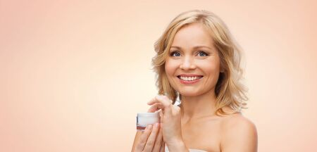 woman face cream: beauty, people, skincare and cosmetics concept - happy woman with cream jar over beige background
