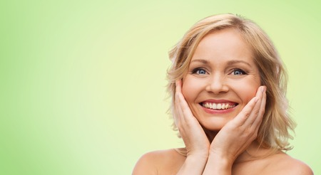 natural beauty: beauty, people and skincare concept - smiling woman with bare shoulders touching face over green natural background