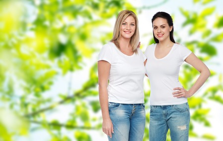 friendship, diverse, body positive and people concept - group of happy different women in white t-shirts hugging over green natural summer background
