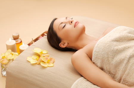 spa and beauty concept - woman in spa salon lying on the massage desk