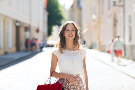 sale, consumerism and people concept - happy young woman with shopping bags walking along city street Stock Photo