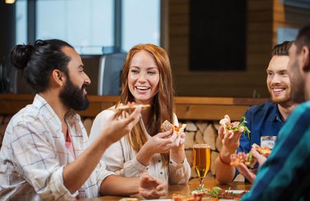 alimentos y bebidas: ocio, alimentación y bebidas, la gente y el concepto de vacaciones - sonriendo amigos comiendo pizza y bebiendo cerveza en el restaurante o pub
