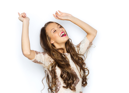 people, style, holidays and fashion concept - happy young woman or teen girl in fancy dress with sequins and long wavy hair dancing at party Stock Photo