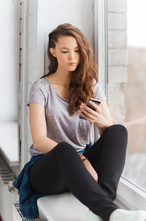 mensen, technologie en tieners concept - triest ongelukkig mooie tiener meisje, zittend op de vensterbank met smartphone en sms'en