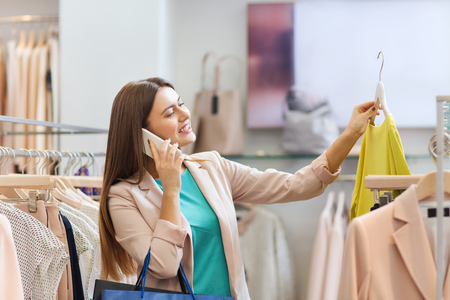 clothes hangers: sale, consumerism, fashion, communication and people concept - happy young woman with shopping bags choosing clothes and calling on smartphone in mall or clothing store