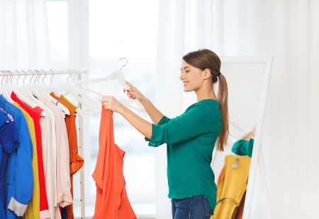 shirt hanger: clothing, fashion, style and people concept - happy woman choosing clothes at home wardrobe