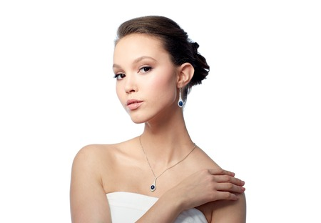 beauty, jewelry, wedding accessories, people and luxury concept - beautiful asian woman or bride with earring and pendant