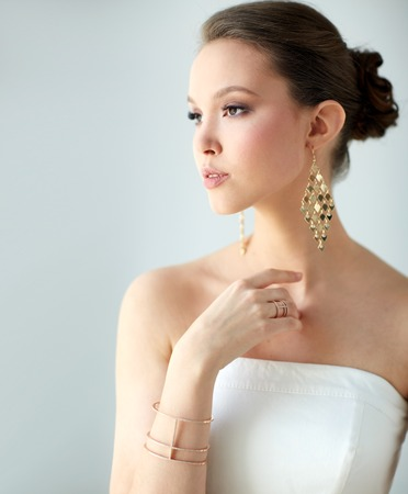 wristlet: beauty, jewelry, wedding accessories, people and luxury concept - beautiful asian woman in white dress or bride with golden earrings and bracelet Stock Photo