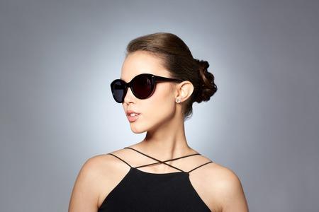 액세서리, 안경, 패션, 사람과 명품 개념 - 회색 배경 위에 우아한 검은 색 선글라스에 아름 다운 젊은 여자